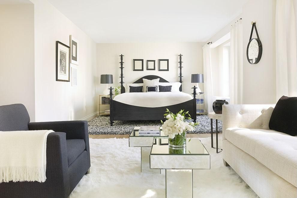 L-shaped bedroom in black and white decor. Walls are white, bed frame is black with white covering