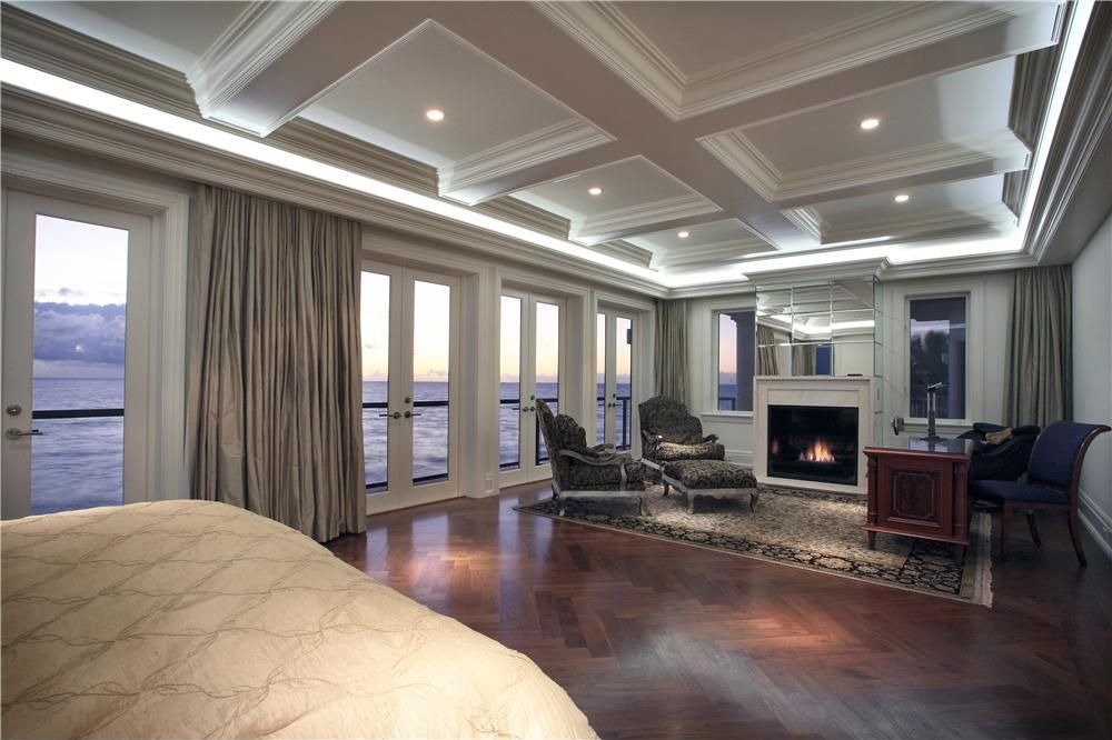 Spacious master bedroom with multiple glass doors leading to balcony overlooking the water
