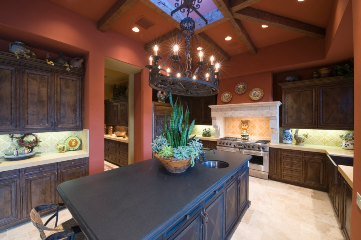Kitchen with cathedral ceiling painted red highlighting large dark island in the center of dark brown cabinets and stainless steel appliances