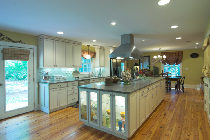 The kitchen island is the star of this kitchen with glass cabinetry with inside lighting. Cabinets are white with wood flooring and light yellow walls