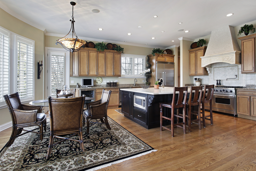 Open concept kitchen with dining area on large rug. Kitchen uses extensive natural wood design with darker toned island