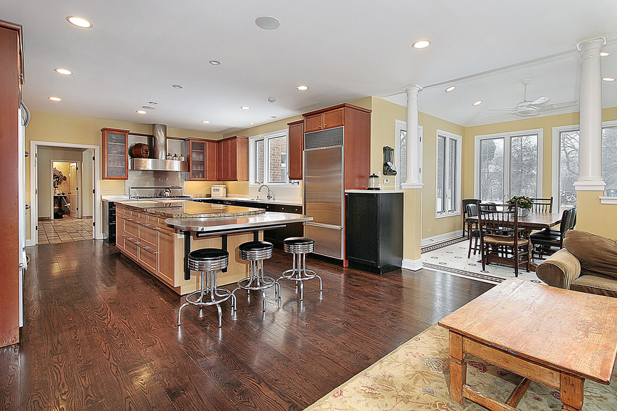 Multi color kitchen with light yellow walls, wood cabinetry, dark wood