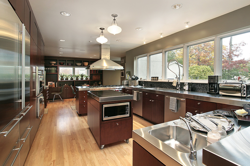 Custom kitchen design with stainless steel counter tops sitting on natural wood cabinets offset with stainless steel appliances and light wood floor. Bank of windows provide natural light thoughout