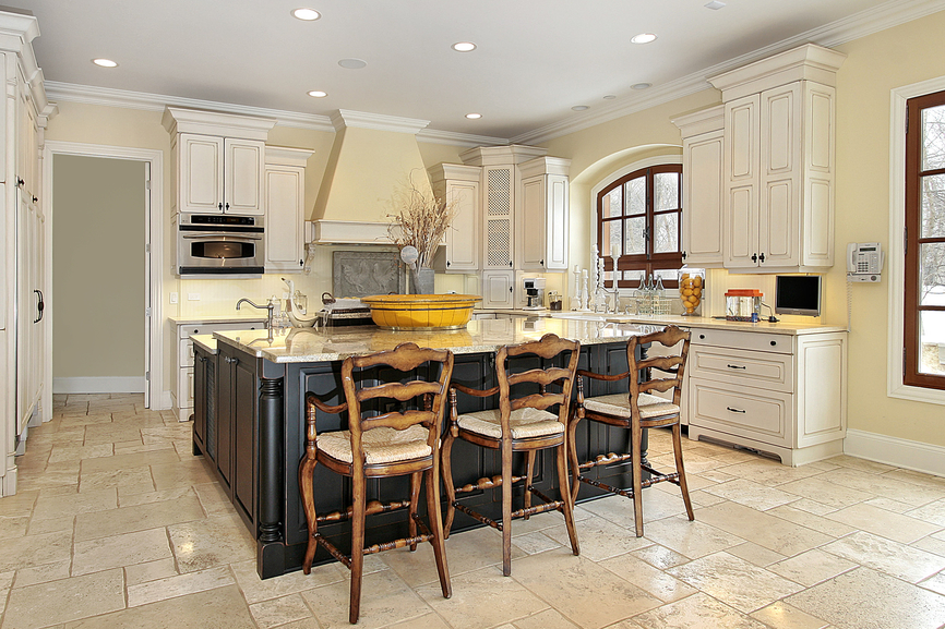 Bright kitchen with light yellow walls, white cabinets with dark two-level kitchen island with large elevated eat-in section