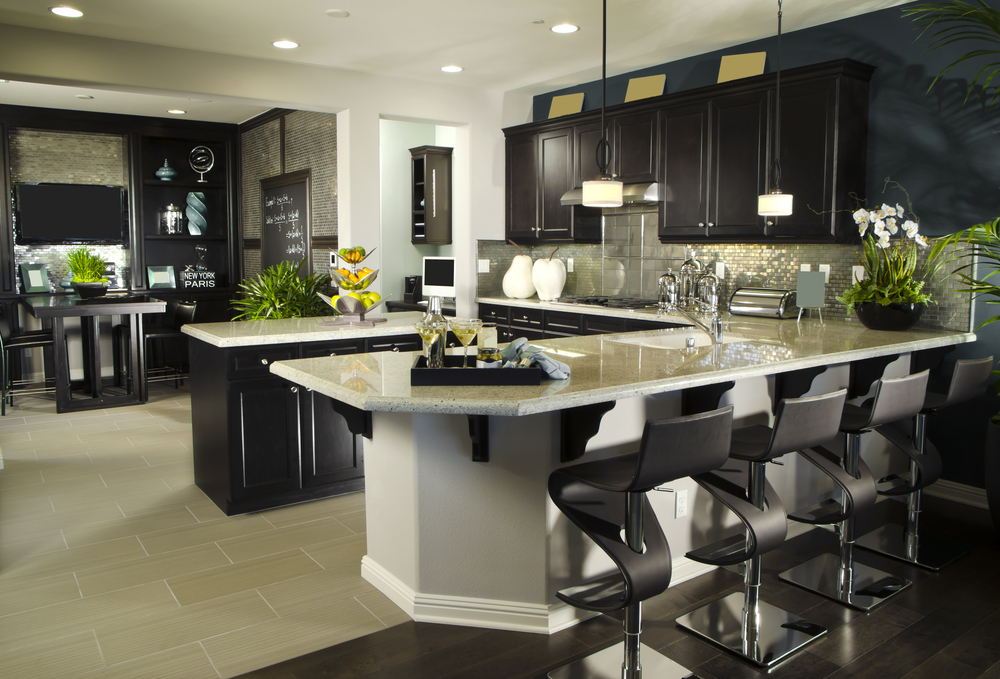 U-shaped luxury kitchen in dark brown and light grey. Kitchen is situated in open concept living space opening up to the dining and living rooms