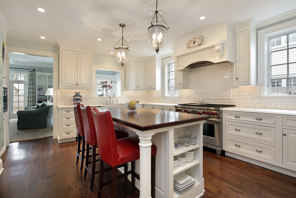 custom kitchen island with red stools sits in the center of the large