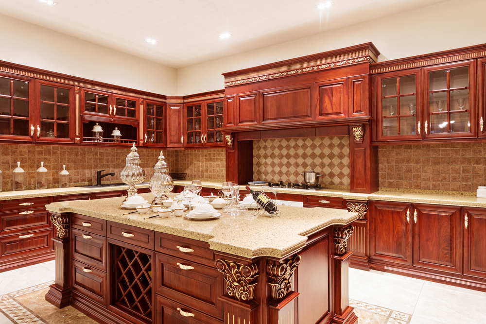 Red-toned wood kitchen cabinets that are intricate in design and include many glass-faced cabinets up top.