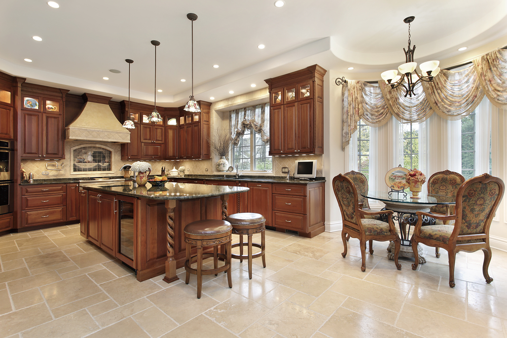 u shaped kitchen in upscale home with wood cabinets tile floor opening up to