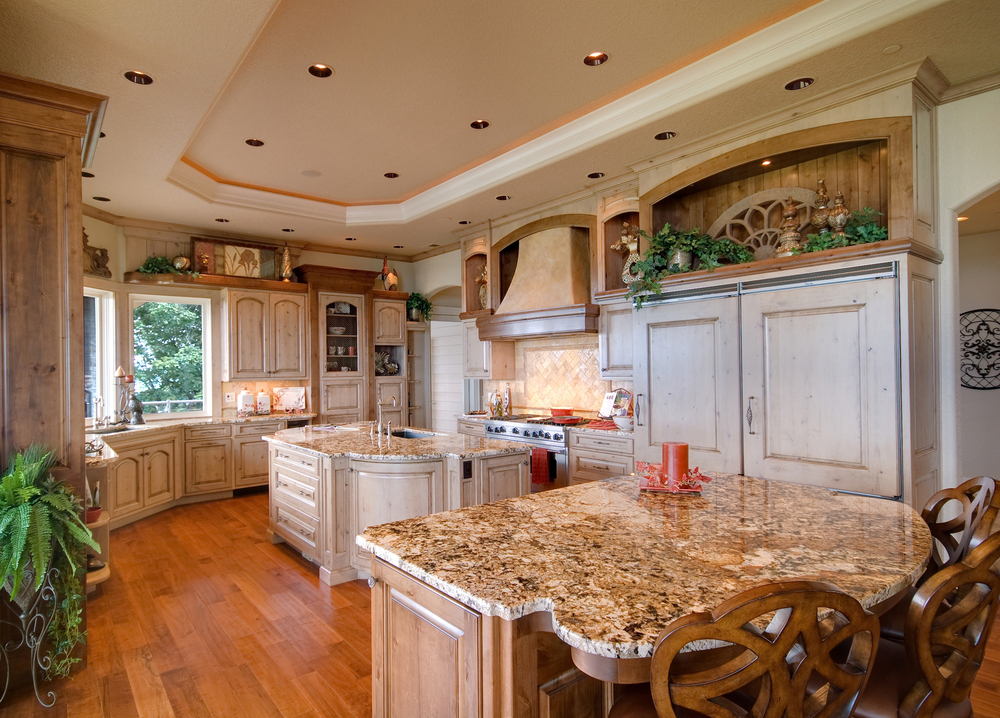 Large country kitchen with curved wall and two islands. Cabinets and one island in white while second island natural wood tone. Tray white ceiling adds to the design.