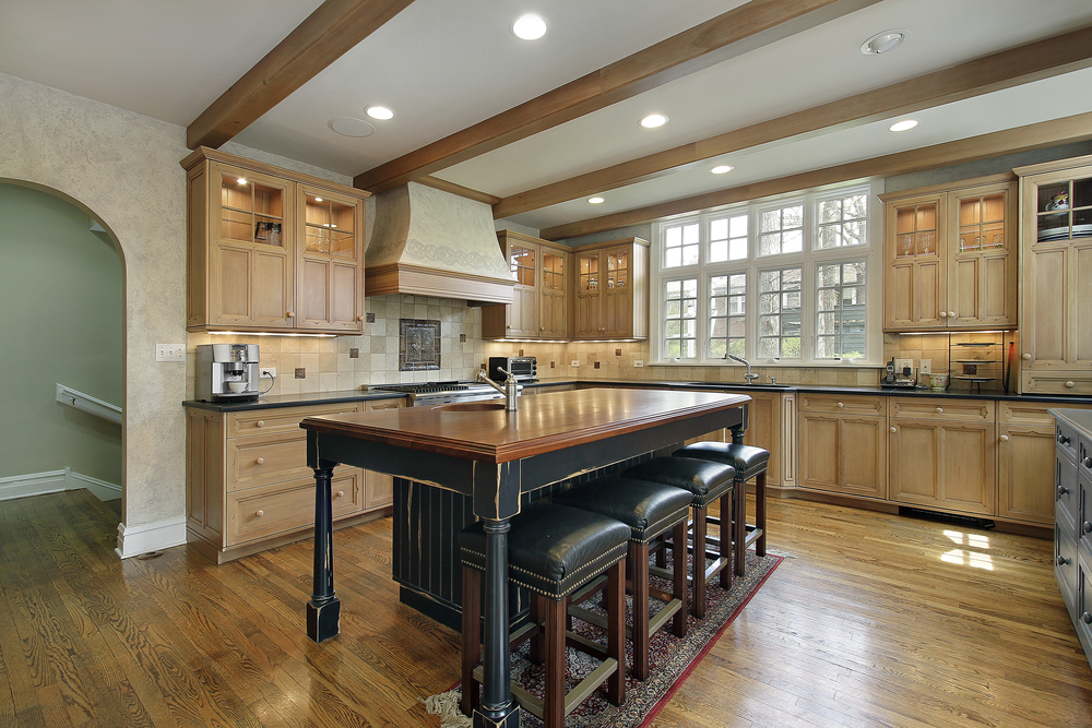 spacious kitchen design with exposed wood beamed ceiling natural wood cabinets and large eat spacious eat kitchen
