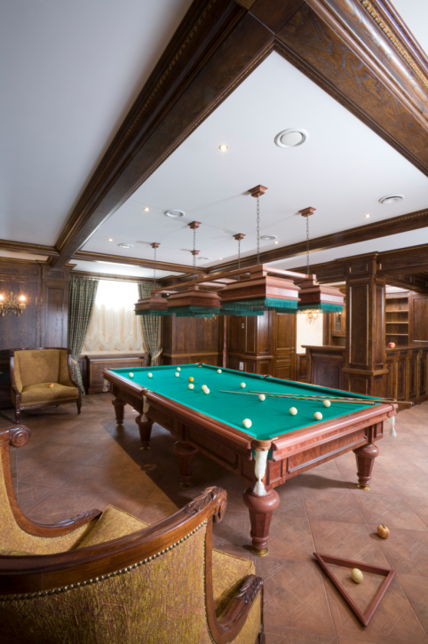 Billiards room with large traditional chairs