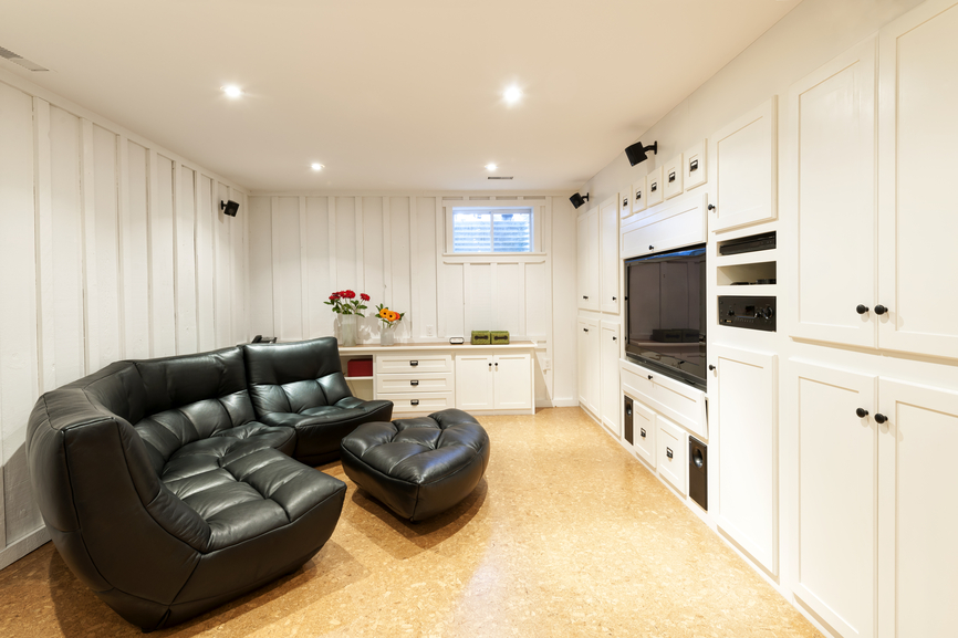 Small white man family room in the basement with large black furniture and light wood flooring
