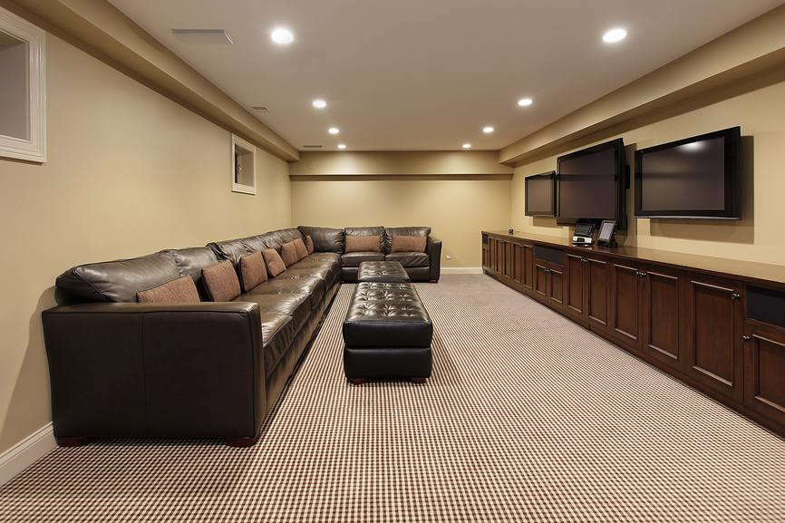 Simple man cave with a huge sectional leather sofa and 3 wall-mounted flat screen televisions