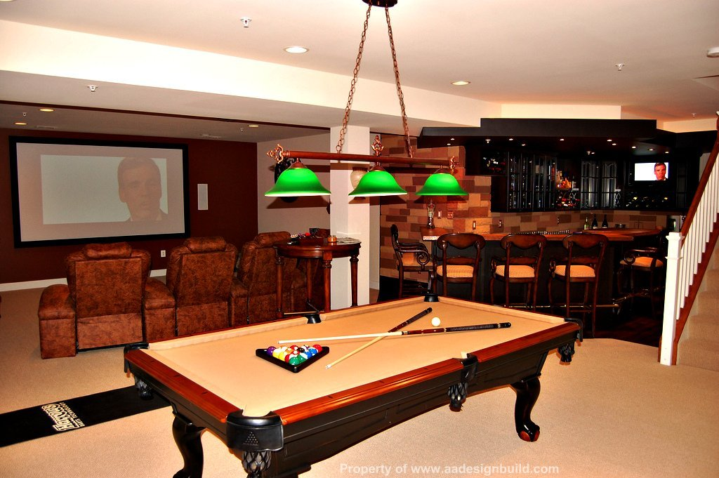 Finished basement with plush theater seating, mounted flat screen TV and billiards table
