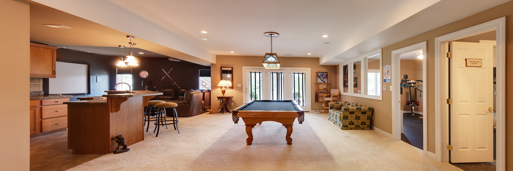 Open concept man cave room design with kitchen, bar, TV room and pool table
