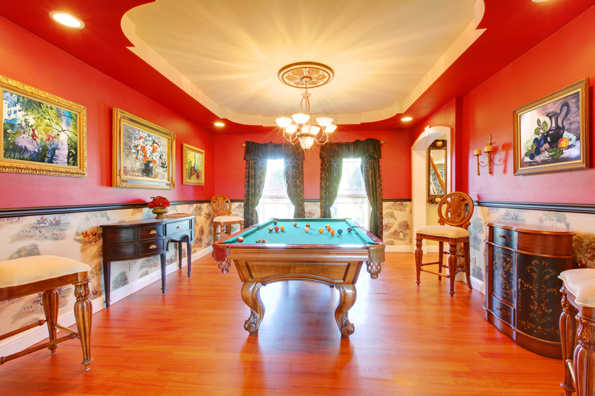 Large billiard game room with hard wood floor.