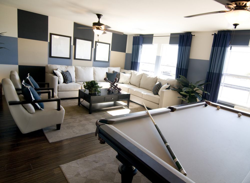 Comfortable man cave with large sectional sofa and billiard table.
