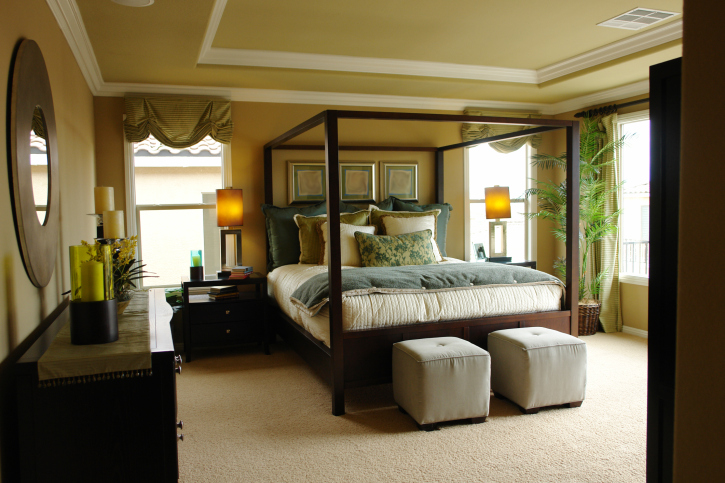 Luxury master bedroom with crown molding, four-poster bed, and dark wood furniture