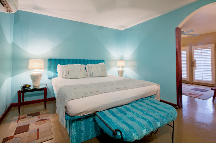 Turquoise master bedroom design with light wood floor