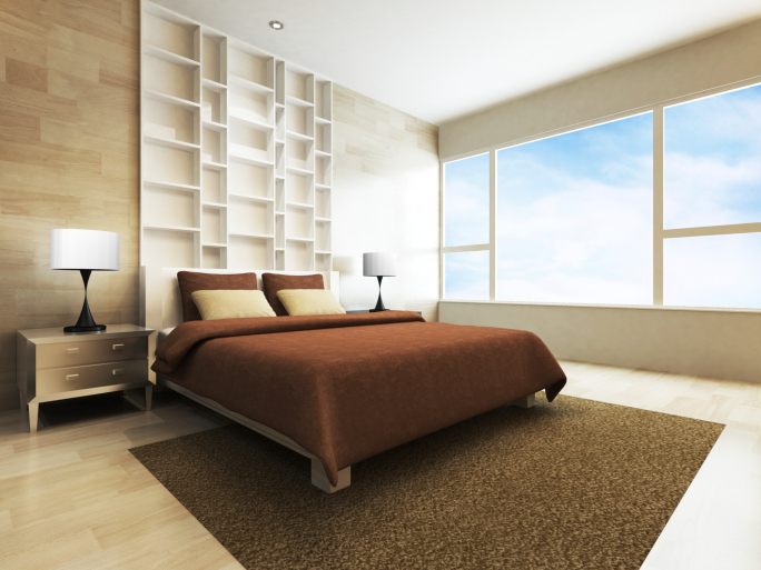 Airy bedroom with large brown rug and built-in white shelving