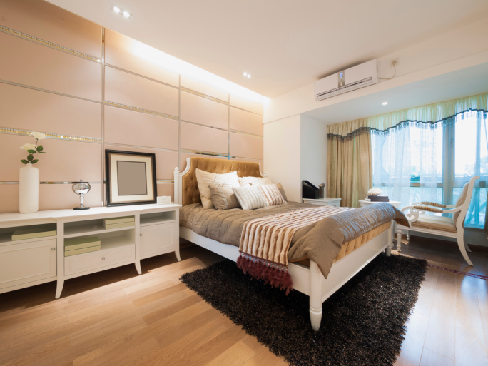 light modern bedroom with white bedroom furniture light wood flooring and small sitting area