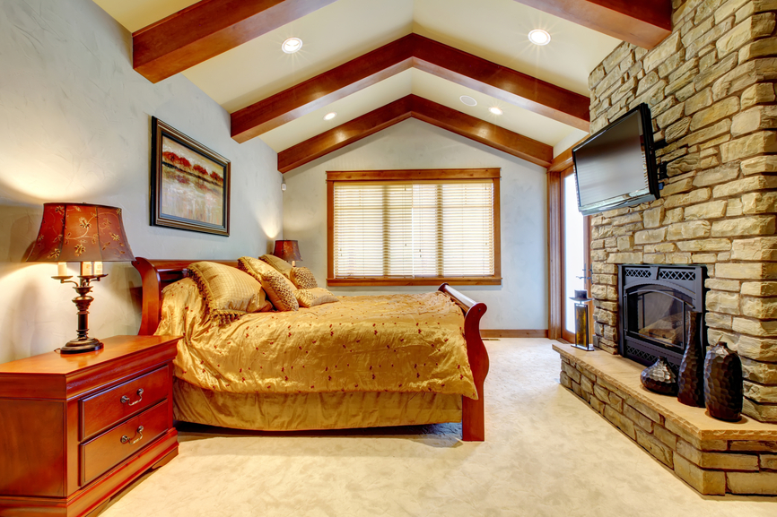 Captivating Expansive Master Bedroom With Vaulted Ceiling And Exposed Beams With Brick  Wall Framing Gas Fireplace