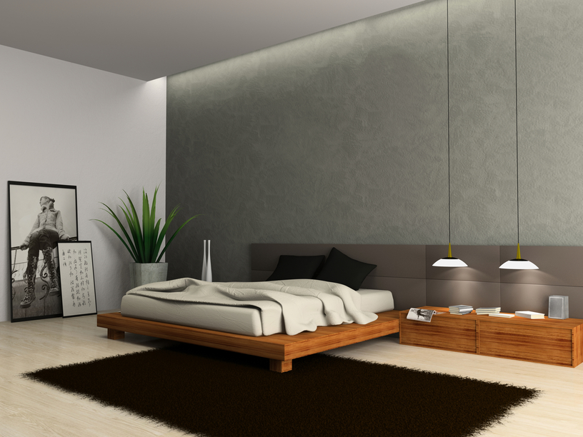 Large bedroom with low wood bed, large black rug and stylish grey walls