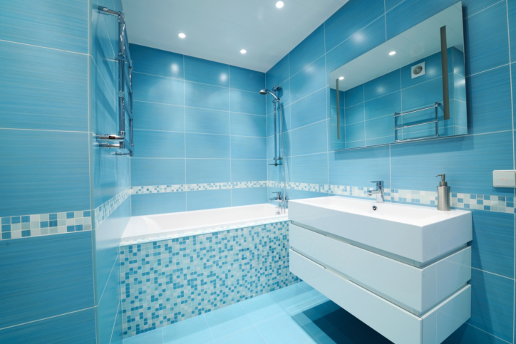 Cool blue modern bathroom with white sink and completely tiled