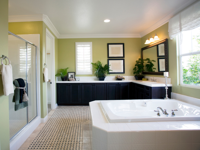 Large luxury bathroom with light green walls, dark cabinetry and white bathtub