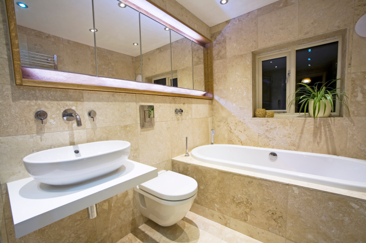 Modern marble bathroom with single white sink and white toilet