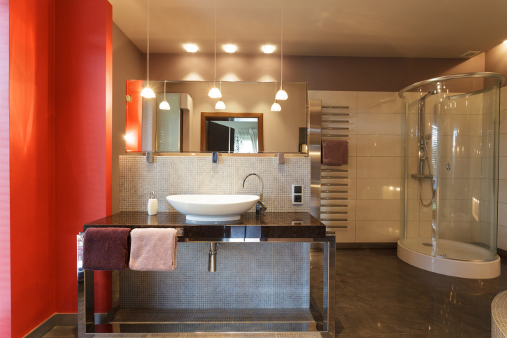 Large red, wood and glass bathroom with round glass shower