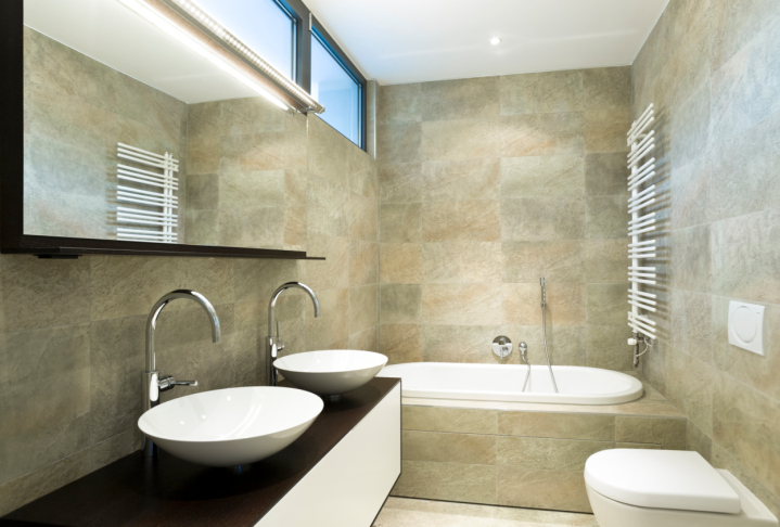 Elegant bathroom with elevated windows, 2 sinks and large white tub - fully tiled