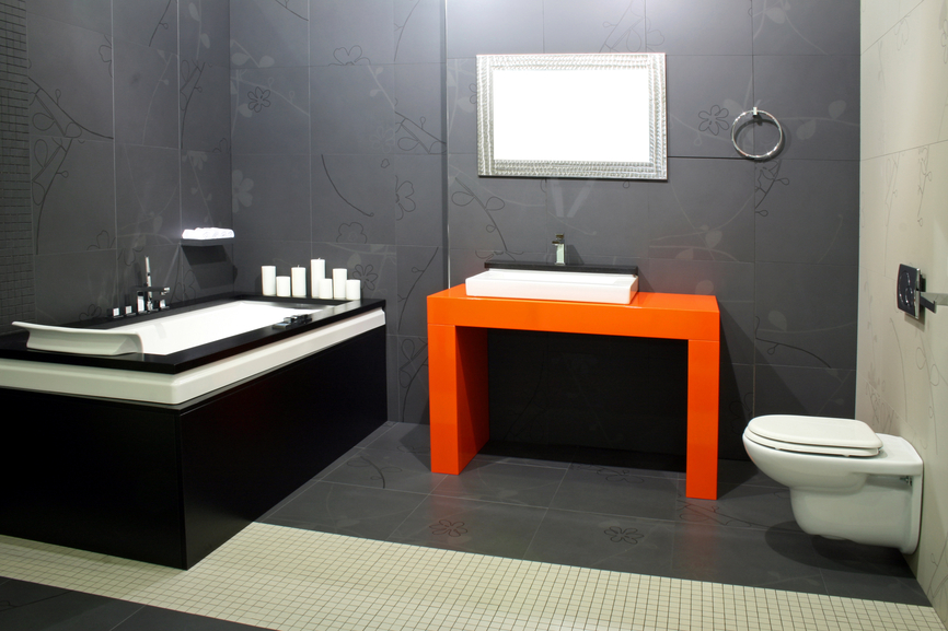 Small dark modern bathroom with orange sink pedestal and black tub