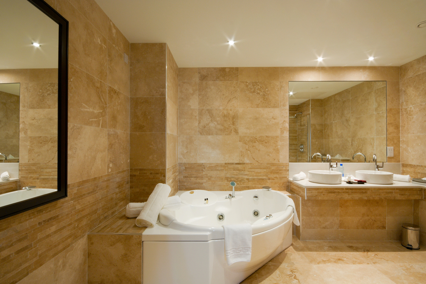 Large marble bathroom with multiple mirrors and large white jacuzzi bathtub