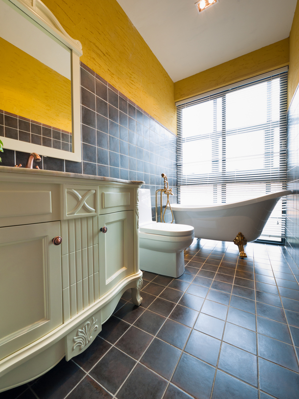 Stylish yellow and dark-tone bathroom with white cabinets, toilet and tub