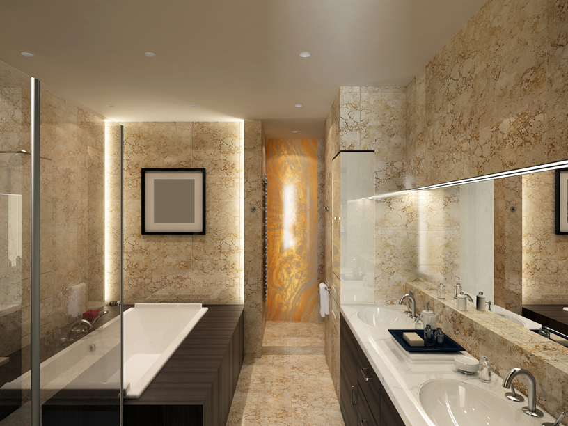 Long and narrow marble bathroom with two sinks, large white tub and glass shower