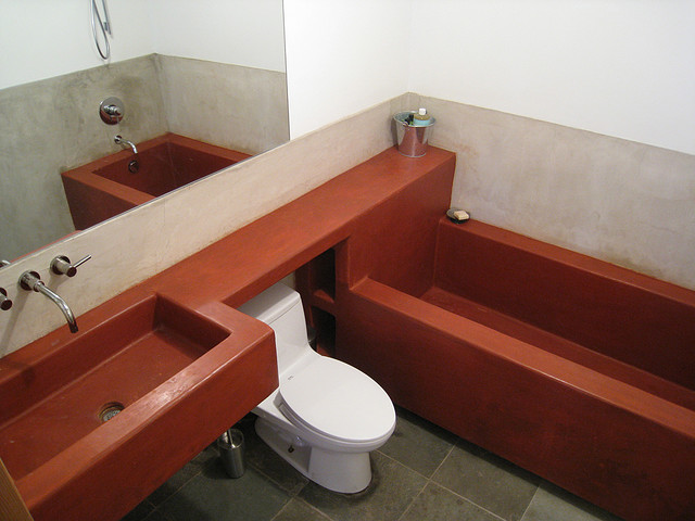 Concrete bathroom with concrete sink and tub in a rust color scheme
