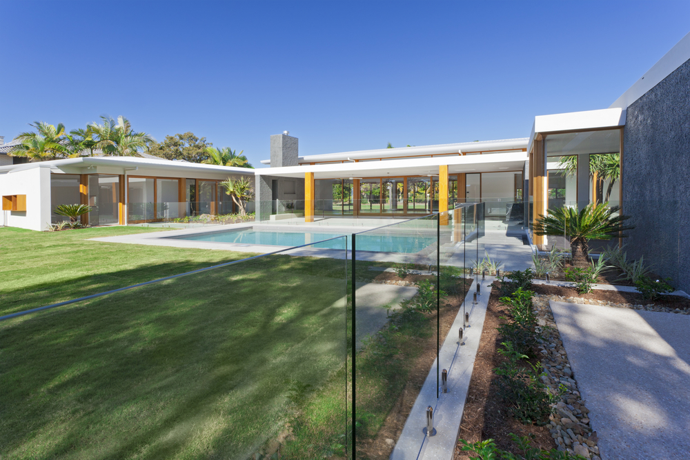 1-story modern contemporary home with wood pillars and large courtyard swimming pool