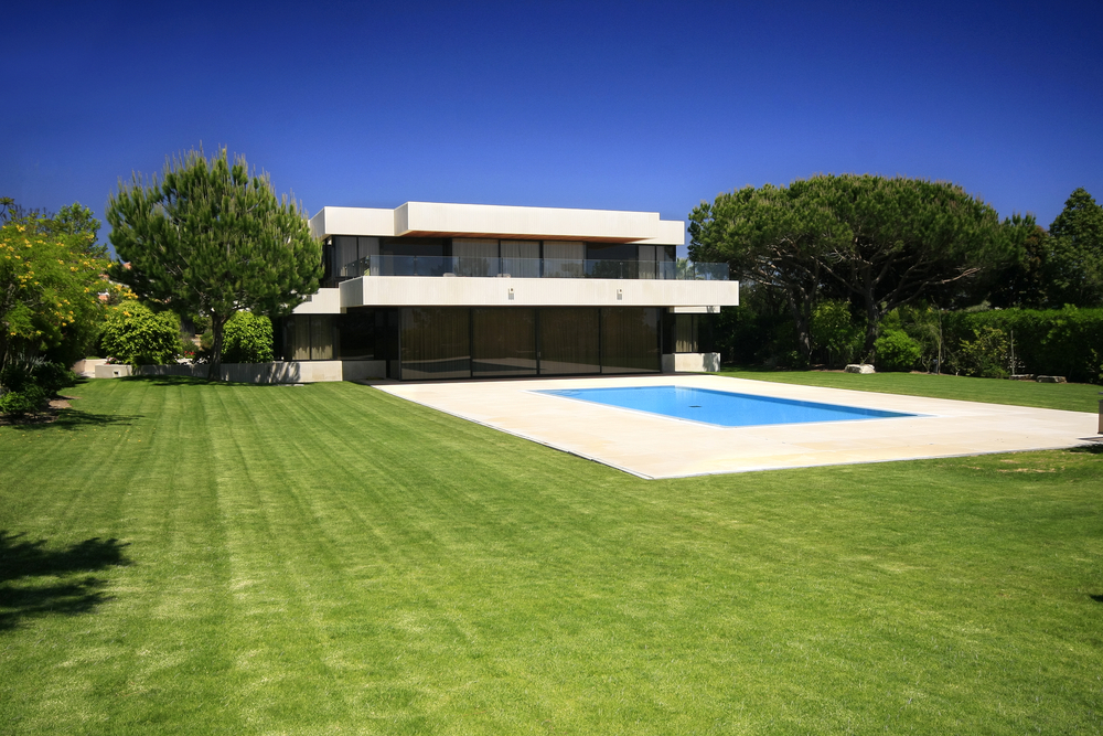 White modern home with dark windows on large grass lot with in-ground swimming pool