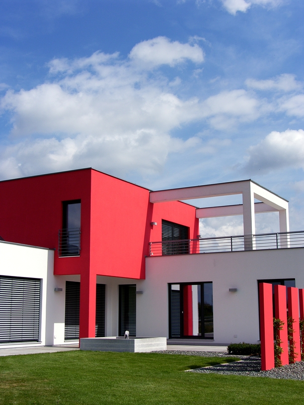 Red and white modern home built in a series of cubes with large upper floor roof-top deck
