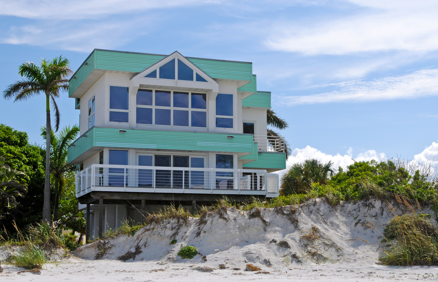 Large 2-story modern beach house built on sand dune with wrap-around deck and green roof