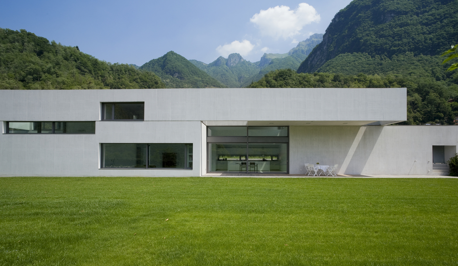 Modern mansion in white with large closely cropped grass yard situated at the base of mountain