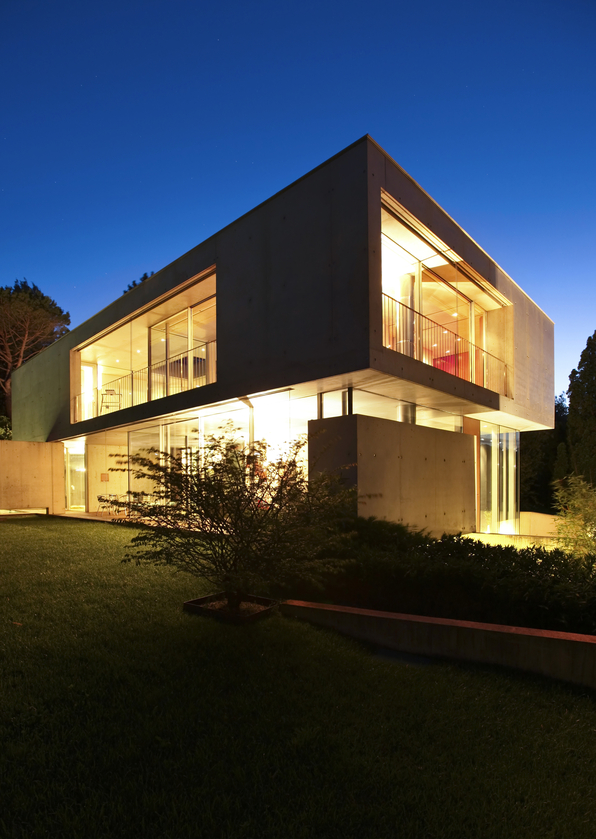 Modern home design illuminated at night. Home is cube-shaped
