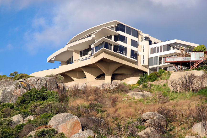 Large contemporary 3-story home on cliff-side built on concrete stilts with multiple decks