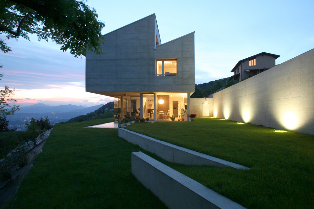 Geometric top heavy concrete home built on edge of steep slope