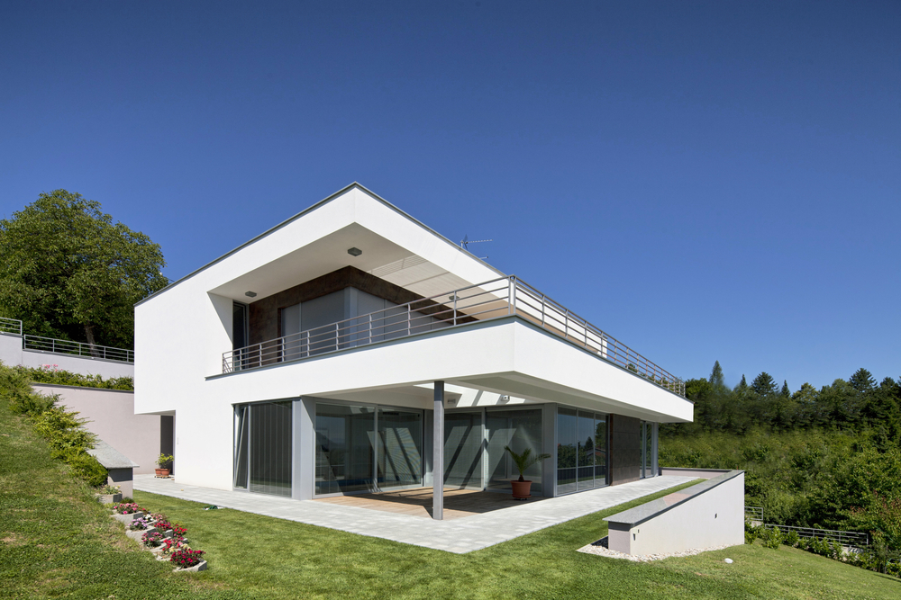 White home with floor-to-ceiling glass built on hillside