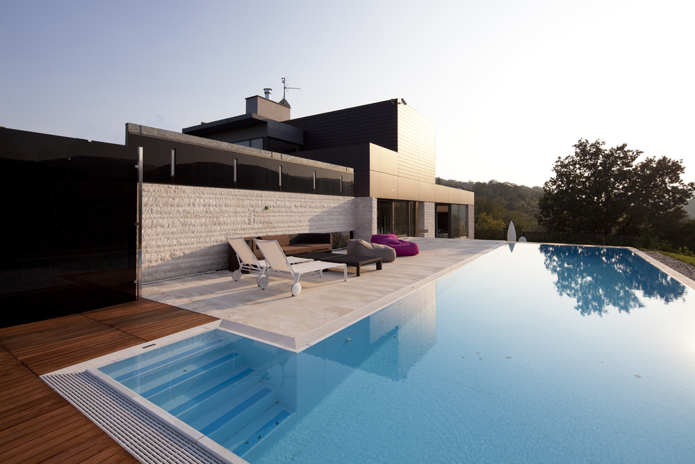 Modern brick and wood home with floating patio over swimming pool
