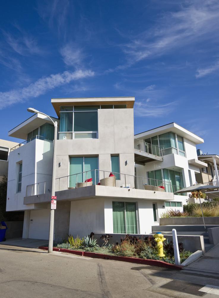 Vertically rambling geo-shape white modern home built on sloped street