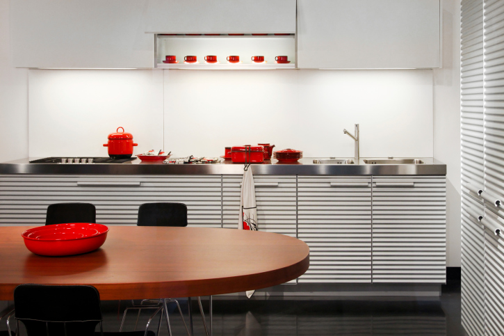Small silver and white kitchen with white walls and red eat-in dining table
