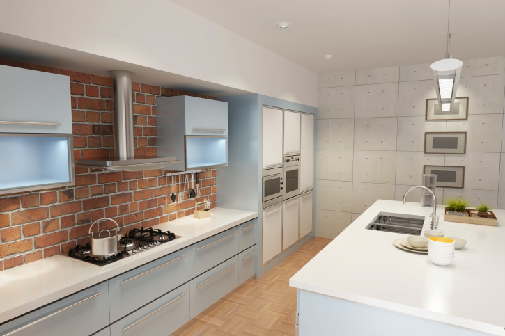 Silver and white kitchen with brick wall and all-white island and light wooden floors